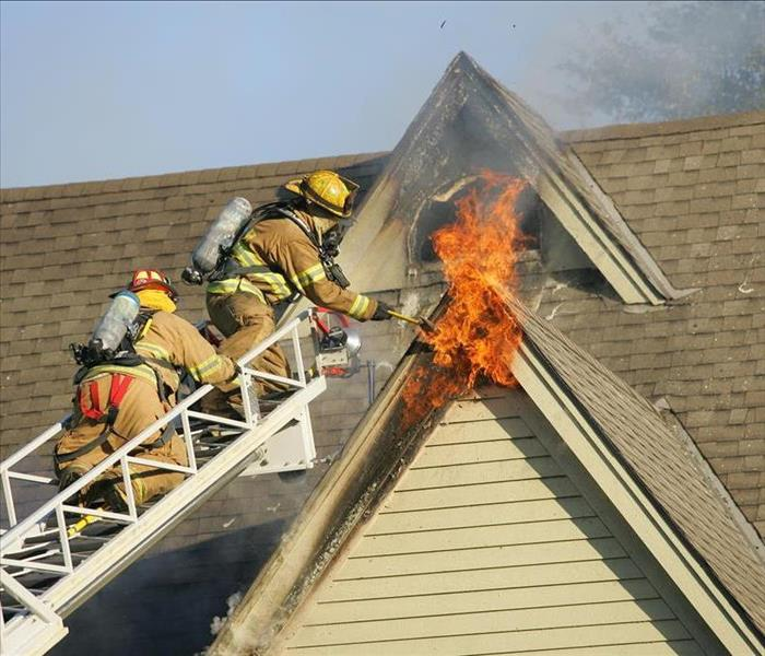 firemen fighting fire on roof
